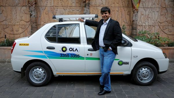 FILE PHOTO: Bhavish Aggarwal, CEO and co-founder of Ola, an app-based cab service provider, poses in front of an Ola cab in Mumbai. (REUTERS)
