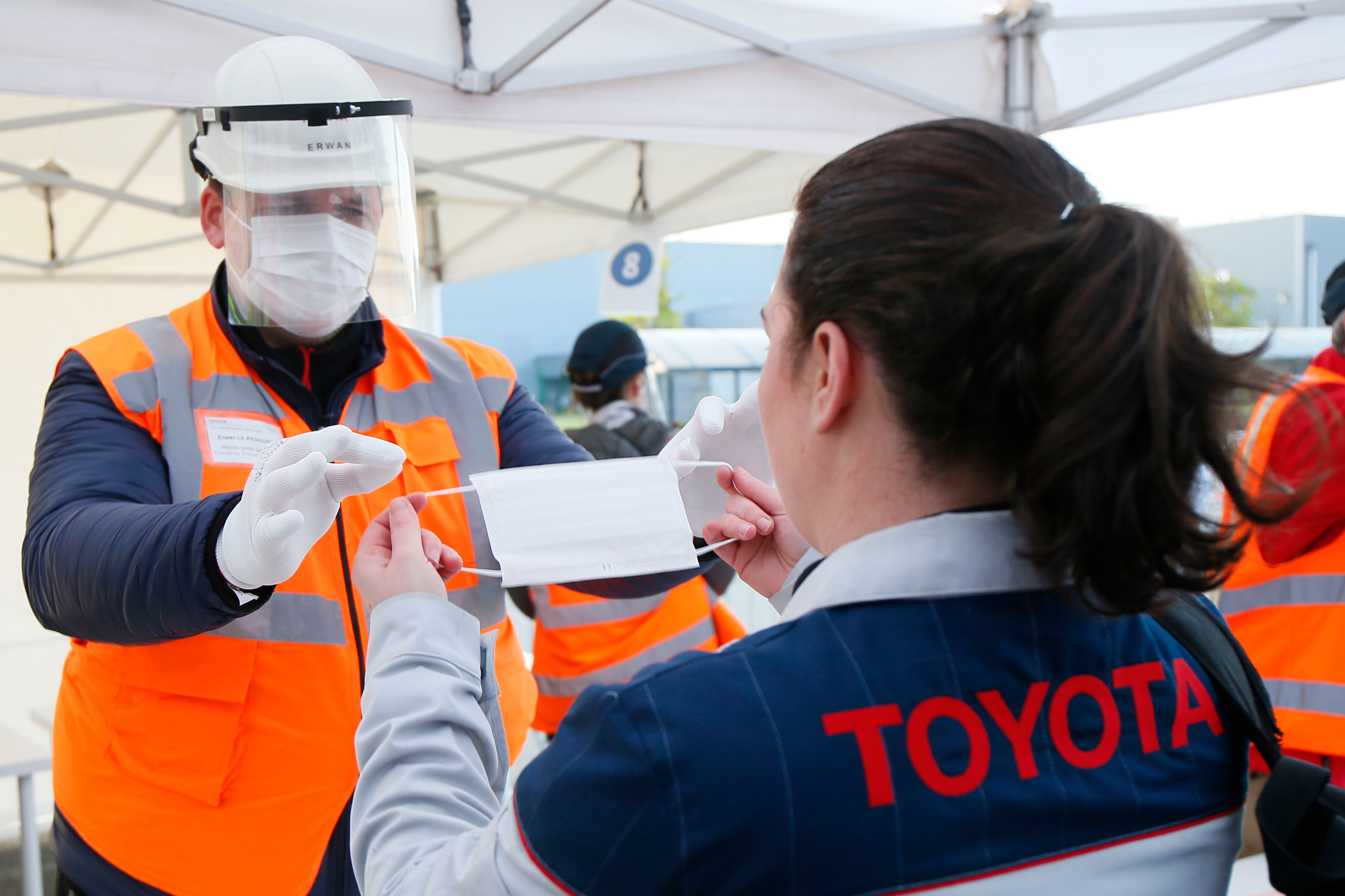 As workers return to Toyota's factory in Onnaing, northern France, they are being instructed on ways to protect themselves from infection in the workplace. Here, an employee hands over a protective mask to a worker while telling her how to use it. (AP)