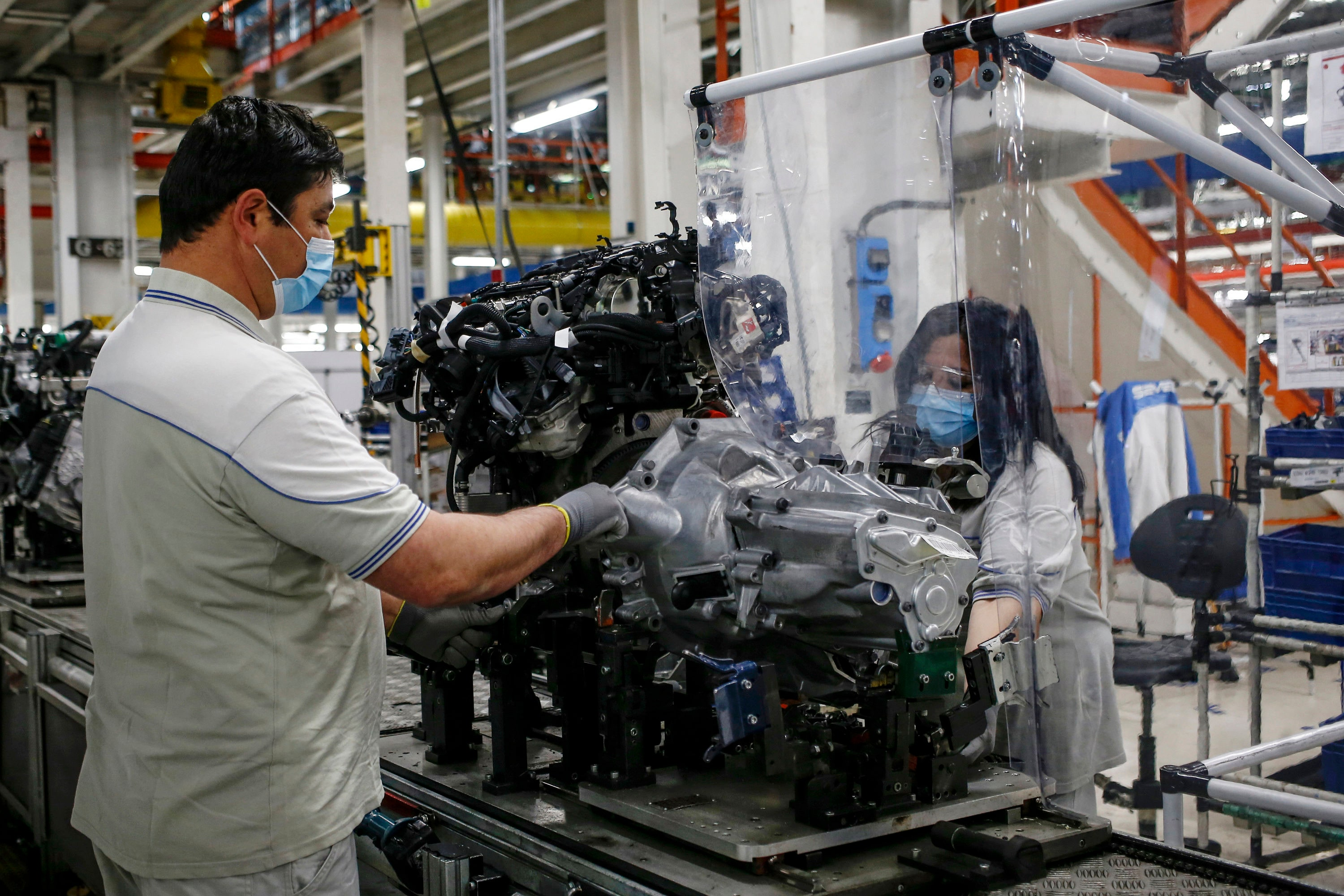 As Fiat resumes production work at its plant in Italy, preparations for worker safety have been given utmost priority. Plastic sheets have been laid between two workers needing to face each other to perform their task in order to help avoid transmission of infection. (AP)