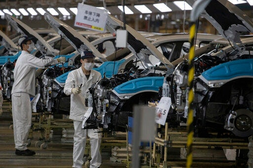 In this photo dated April 8, employees work on a car assembly line at the Dongfeng Honda factory in Wuhan in central China's Hubei province. The workers can be seen wearing protective gears like masks and gloves in line with safety protocols. (AP)