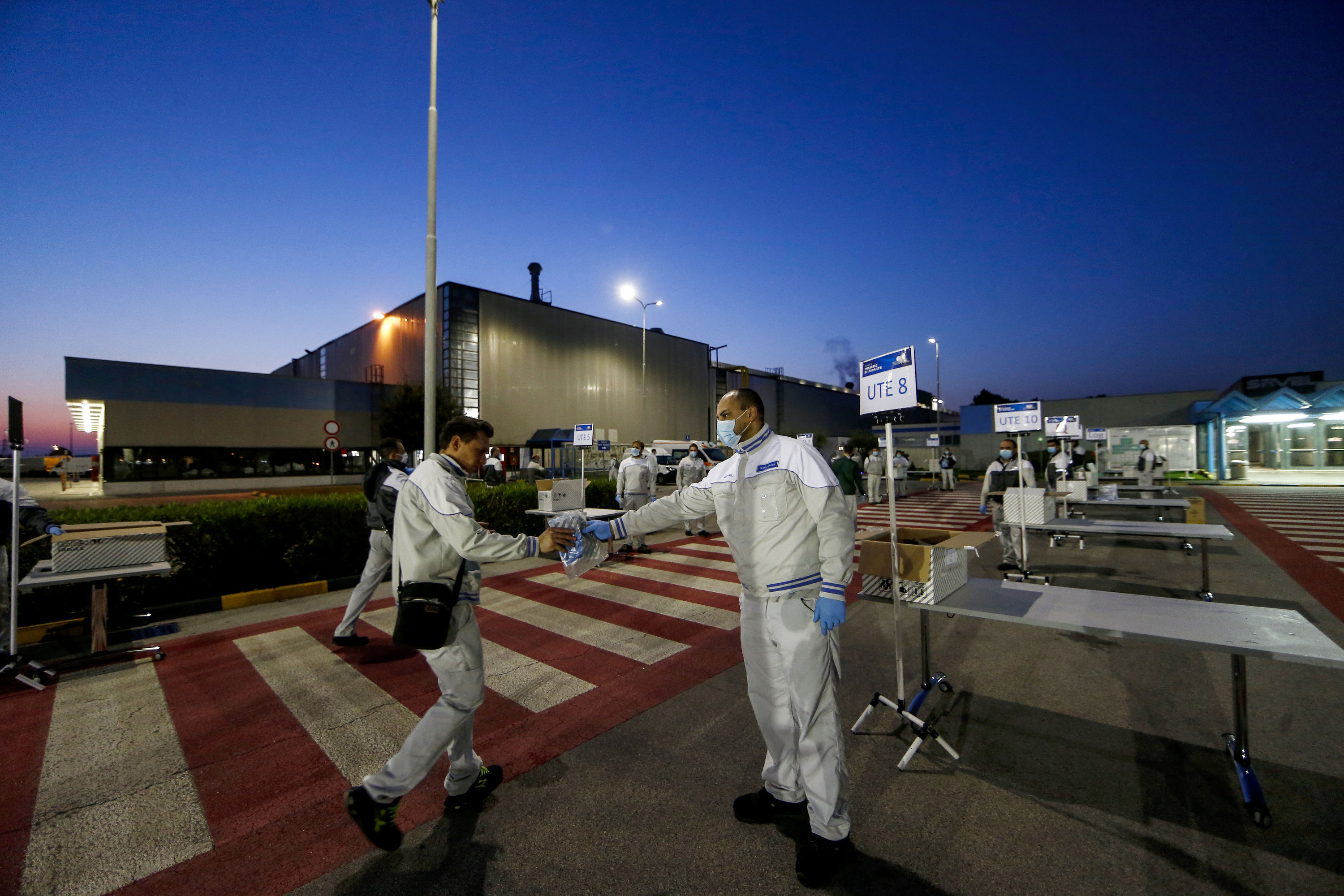 As workers return to work at Fiat's Italian plant, safety kits with rubber gloves and face masks are being distributed at the entrance. The personal protective gear will help workers avoid transmission of infection at workplace.  (AP)