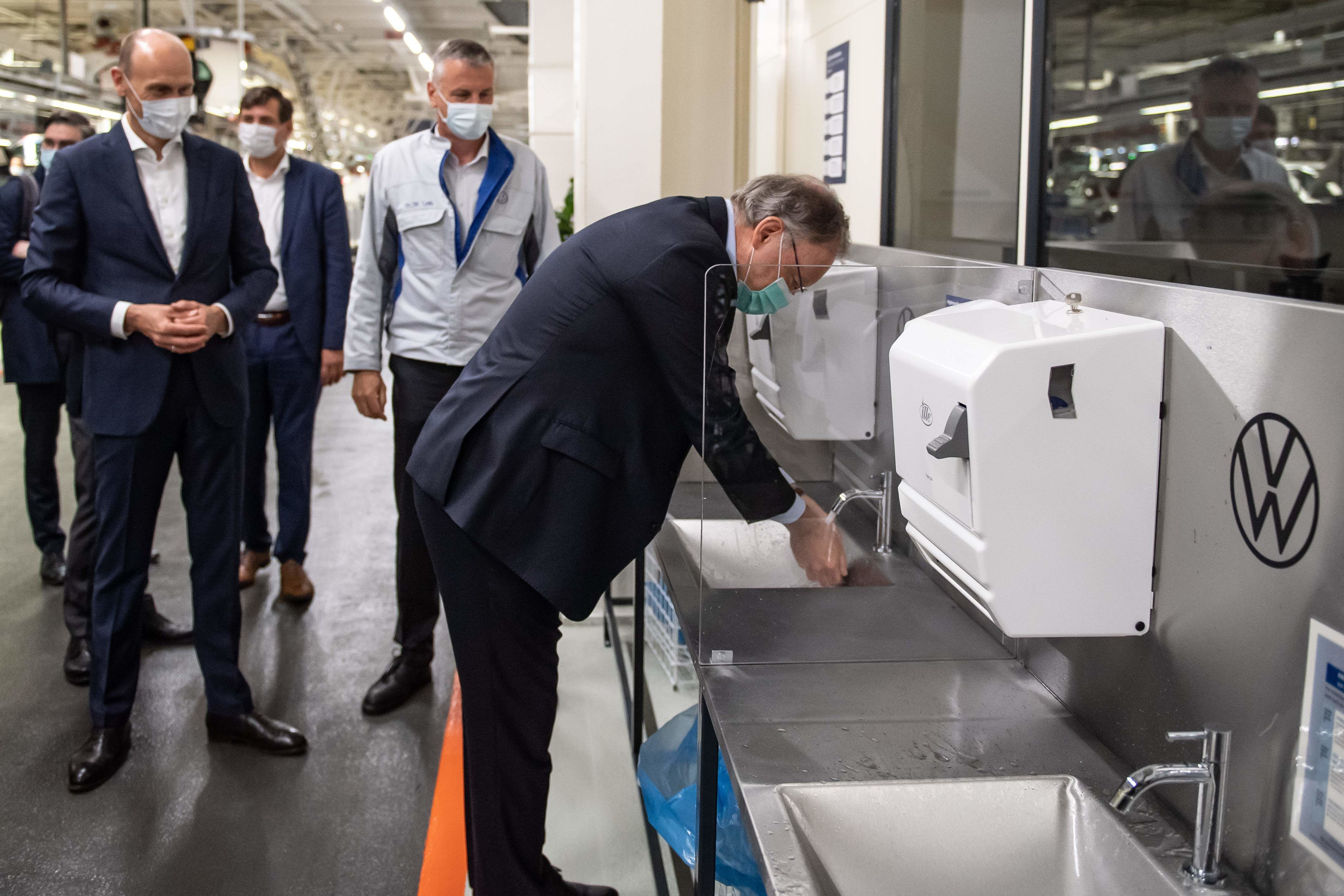 Lower Saxony's State Premier Stephan Weil (R) washes his hands as he visits the plant of Volkswagen Germany. In line with essential safety protocols, Volkswagen has installed wash basins where any visitor or worker can keep washing hands from time to time. (AFP)