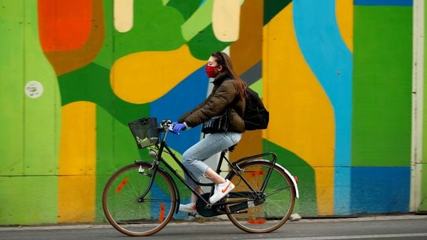 FILE PHOTO: A woman wearing a protective mask rides her bicycle during the coronavirus disease (COVID-19) outbreak, in Brussels, Belgium. (REUTERS)