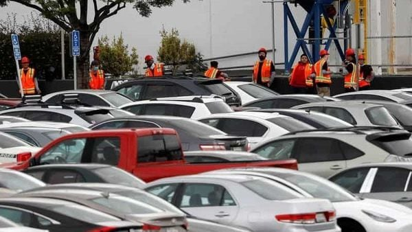 Workers in orange vests are seen outside Tesla's primary vehicle factory after CEO Elon Musk announced he was defying local officials' restrictions against the coronavirus disease (COVID-19) by reopening the plant in Fremont, California, U.S. May 12, 2020. REUTERS/Stephen Lam (REUTERS)