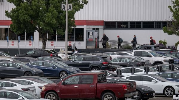 After CEO Elon Musk restarted production at Tesla's only U.S. car plant, workers were seen entering the facility on May 11. The parking lot outside the assembly plant was near to full. (Bloomberg)