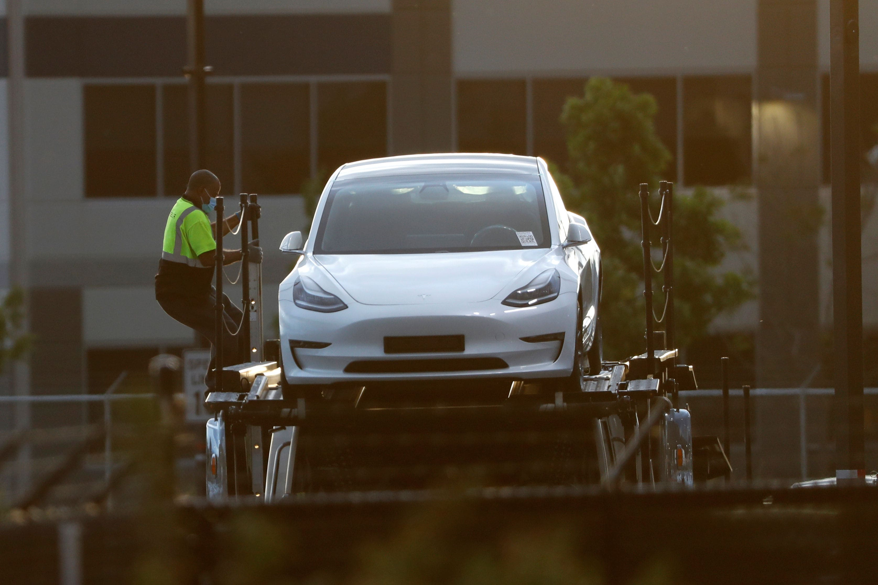 A Tesla worker can be seen descending from the top deck of a car carrier trailer carrying Tesla electric vehicles at its primary factory after production resumed. CEO Elon Musk has openly acknowledged that he is risking arrest for himself and his employees by defying orders to remain shut. (REUTERS)