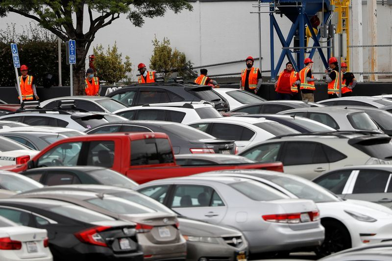 Tesla workers in orange vests are seen outside its primary vehicle factory after the factory was reopened for production. CEO Elon Musk had tweeted that he will be going against Alameda County rules and be on the line with everyone else. (REUTERS)