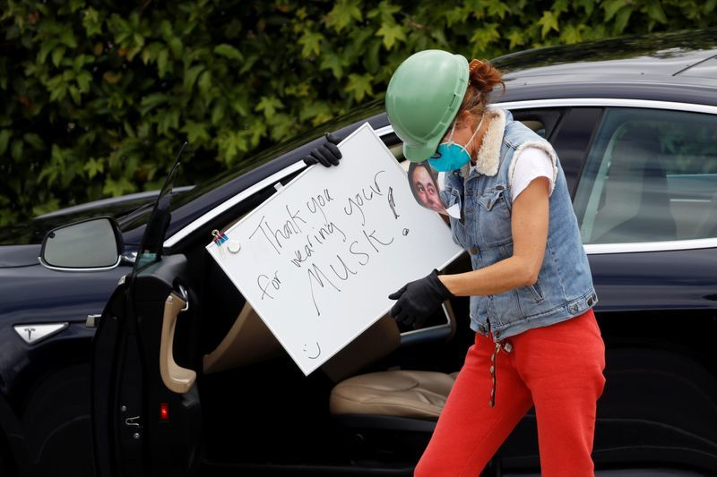 A demonstrator holds a sign outside Tesla's primary vehicle factory in Fremont, California after CEO Elon Musk announced he was defying local officials' orders to stay shut, The placard read,