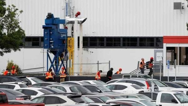 Workers in orange vests are seen outside Tesla's primary vehicle factory in Fremont, California. (REUTERS)