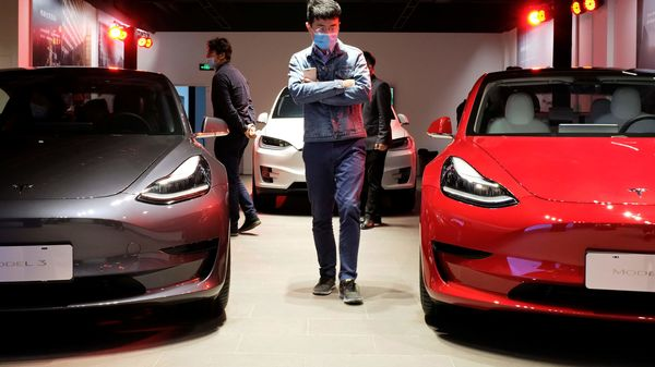 A man wearing a face mask following the coronavirus disease (COVID-19) outbreak walks by Tesla Model 3 sedans and Tesla Model X sport utility vehicle at a new Tesla showroom in Shanghai, China May 8, 2020. Picture taken May 8, 2020. REUTERS/Yilei Sun (REUTERS)