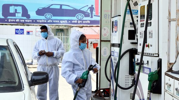 Employees of Auto Motives Hindustan Petroleum petrol pump wearing Personal Protective Equipment Kit (PPE Kit) while attending to the customers, in New Delhi.