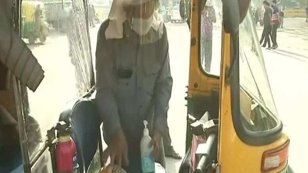 An auto driver in Delhi, armed with mask, face shield and sanitizer, gets ready to get back into his vehicle and provide transportation service in Delhi. (ANI photo)