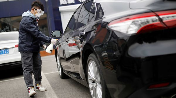 FILE PHOTO: A staff member disinfects a vehicle at a service centre of car-hailing service Didi Chuxing in China. (REUTERS)