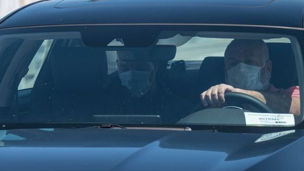 A driver and passenger wearing protective masks exit the ride sharing pickup area. (Bloomberg)