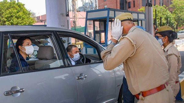 Noida: Police personnel check a commuter travelling from Delhi to Noida during the nationwide lockdown to curb the spread of coronavirus. (PTI)