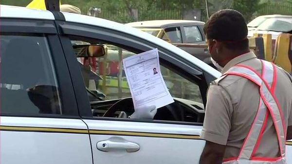 A policeman checking pass of a commuter at Delhi-Gurugram border to control the movement of vehicles during coronavirus lockdown, in Gurugram.