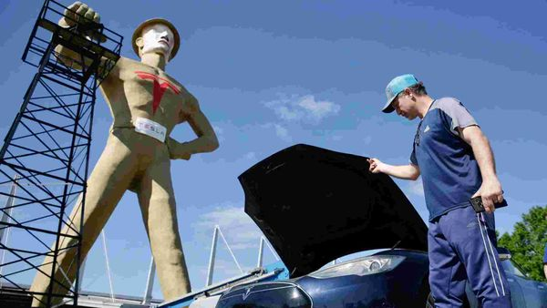Andrew Nelson lifts the hood of his Tesla Model S in front of the Golden Driller. Tulsa's iconic Golden Driller statue is joining the effort to help lure automaker Tesla to build its new US assembly plant here. (AP)