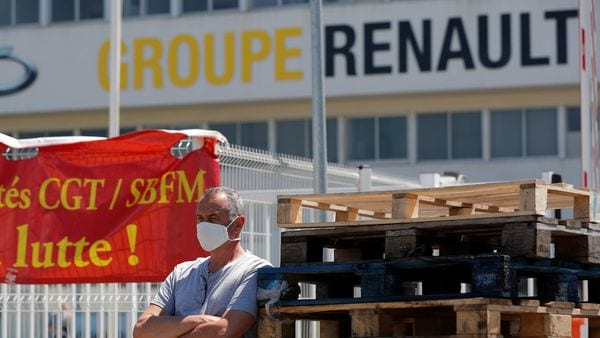 An employee on strike, wearing a protective face mask, stands next to a banner outside the Fonderie de Bretagne plant, a subsidiary of Groupe Renault, to protest against its possible closure in Caudan, France. (REUTERS)