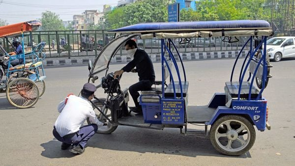 A traffic police officer removes air from the tyre of an e-rickshaw as the driver breaks the lockdown rule during the lockdown 4.0 in New Delhi.