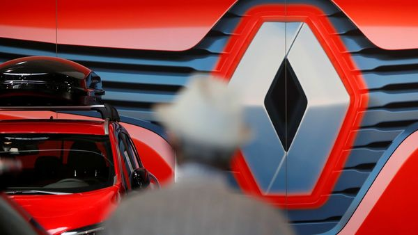 A customer looks at cars in front of a logo of Renault carmaker at a dealership in Nantes, France, May 26, 2020. (REUTERS)