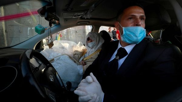 FILE PHOTO: A Palestinian groom, Rafeh Qassim, wears a mask as he sits in a car with his bride on their wedding day amid concerns about the spread of the coronavirus disease (COVID-19), in Ramallah in the Israeli-occupied West Bank April 18, 2020. REUTERS/Mohamad Torokman (REUTERS)