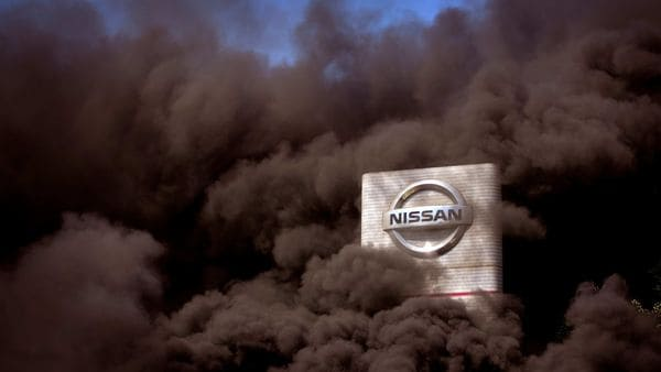 Smoke rises over the Nissan factory as workers burn tires during a protest in Barcelona, Spain, (AP)