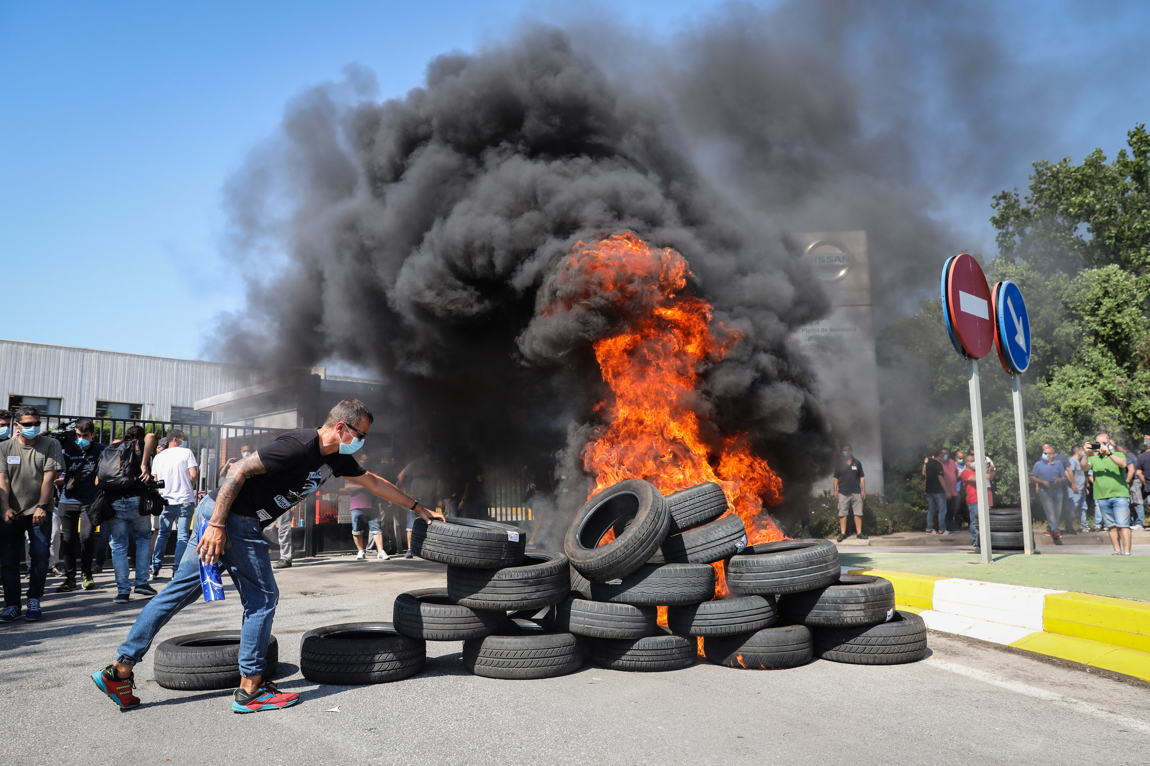 Demonstrators set fire to tyres outside Nissan plant in Barcelona to show their anger over the company's decision to close the plant.  (Bloomberg)