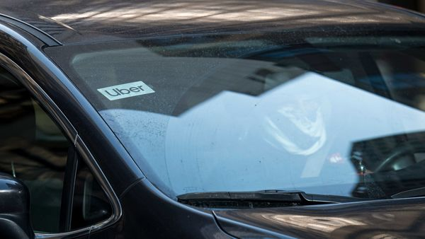 File photo: A driver wearing a protective face covering drives a car displaying Uber Technologies signage on California Street in San Francisco, California, U.S. (Bloomberg)