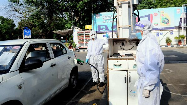 File photo: Petrol pump workers wear protective suit on duty during the nationwide lockdown in New Delhi. (ANI)