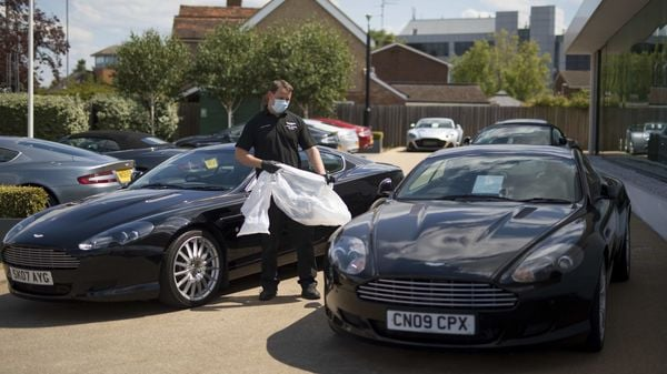 File photo: A worker wearing a protective face maske puts plastic seat covers on Aston Martin automobiles at the Aston Martin Works dealership, operated by the Aston Martin Lagonda Global Holdings Plc, in Newport Pagnell, UK. (Bloomberg)