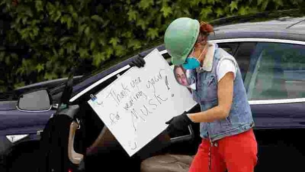 File photo: A demonstrator holds a sign outside Tesla's primary vehicle factory in Fremont, California. (REUTERS)