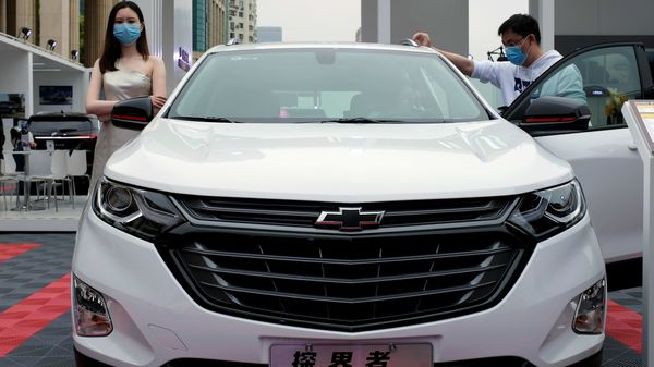 File photo: A model wearing a face mask following the coronavirus disease (Covid-19) outbreak stands next to a Chevrolet vehicle at a sales event in China. (REUTERS)
