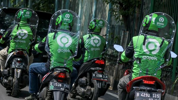 Motorbike taxi drivers drive with backpack-style plastic partitions on to prevent the spread of the coronavirus diseases in Jakarta, Indonesia. (Via REUTERS)