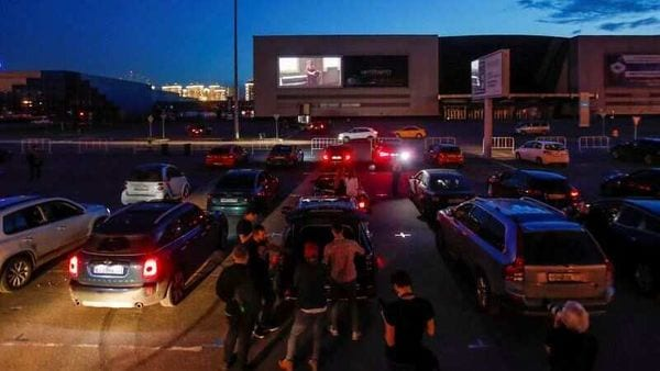 People stand next to parked cars at the Moscow's first drive-in movie theatre as the coronavirus lockdown is lifted in Moscow, Russia June 11, 2020. (REUTERS)