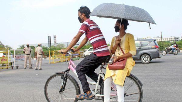 File photo: A woman holds an umbrella on a cycle near Delhi-Gurugram border.
