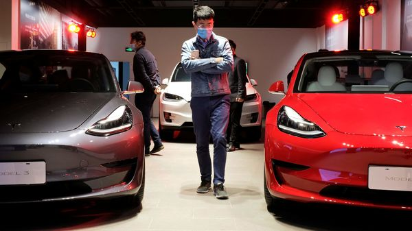 File photo: A man wearing a face mask following the coronavirus disease outbreak walks by Tesla Model 3 sedans and Tesla Model X sport utility vehicle at a new Tesla showroom in Shanghai, China (REUTERS)
