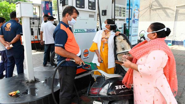 A gas station attendant (C) fills a motorbike tanks at a petrol station in Amritsar. (AFP)