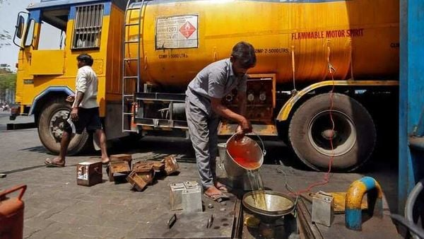 FILE PHOTO: A man pours petrol into an underground tank at a fuel station in Mumbai. (REUTERS)