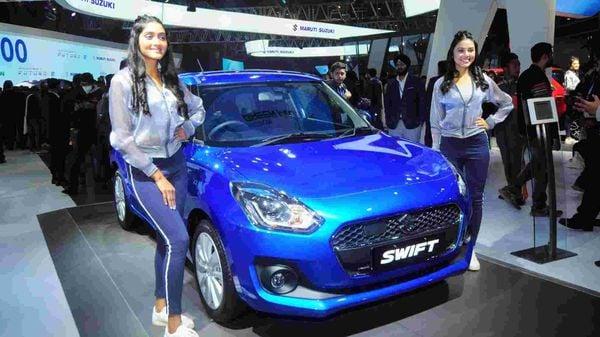 Models pose next to a Maruti Suzuki Swift Hybrid, during the Auto Expo 2020 in Greater Noida. (ANI File Photo)