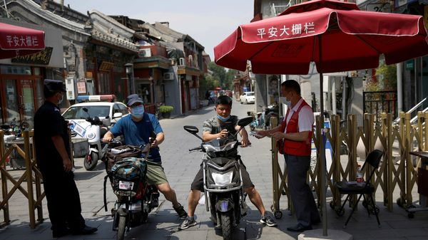 A security guard holds a QR code for registration while a community volunteer takes temperatures of people on their vehicles at an entrance to a hutong, following new cases of the coronavirus disease (COVID-19) infections, in Beijing. (REUTERS)