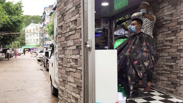 Barber Ko Phyo works at his mobile hair salon in Yangon, Myanmar. (REUTERS)