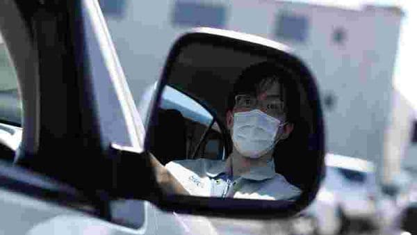 Ryota Kawamata is seen at the driver's seat of a car as the spread of the coronavirus disease continues, in Tokyo. (REUTERS)