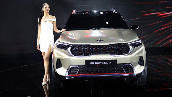 A model poses next to KIA Sonet Concept car at the Auto Expo in Greater Noida. (AP)