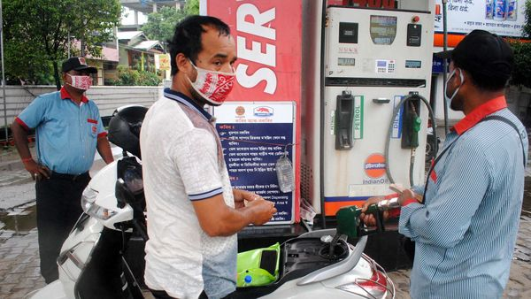 An employee adds fuel in a scooty at a petrol pump in Guwahati.