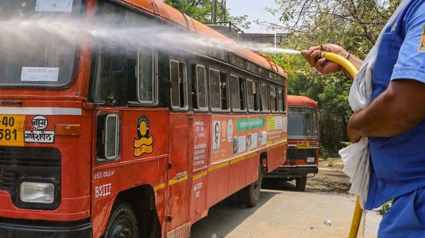 A worker sprays disinfectant on a bus outside at a depot during the fifth phase of Covid-19 lockdown, in Nagpur, Maharashtra. (PTI)