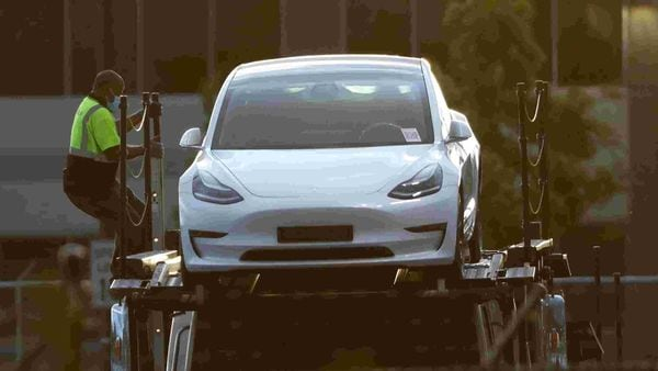 File photo - A Tesla worker can be seen descending from the top deck of a car carrier trailer carrying Tesla electric vehicles at its primary factory. (REUTERS)