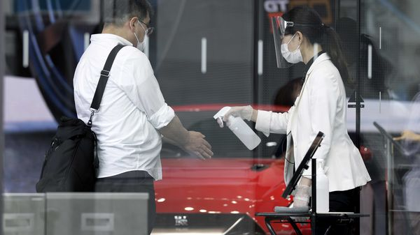 A showroom assistant wearing a protective mask and face shield, right, sprays hand sanitizer into a visitor's hands at the entrance of Nissan Motor's Ginza showroom in Tokyo. (Bloomberg)