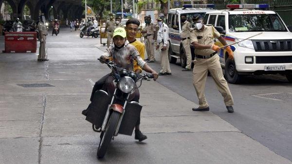 Mumbai: A policeman raises his baton at a commuter during checking amid Covid-19 in Byculla. (PTI)