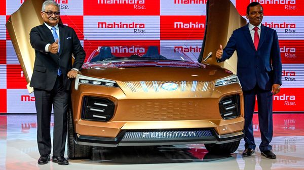 Managing Director of Mahindra and Mahindra Limited Pawan Goenka (right) poses with the Mahindra Funster electric concept vehicle at the Auto Expo 2020. (AFP)