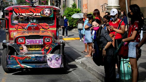 Passengers wearing masks for protection against the coronavirus disease wait for a jeepney with plastic barriers inside to maintain social distancing. (REUTERS)